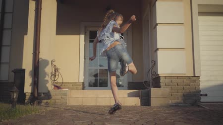 yarda : Cute little girl in headphones spinning and dancing near the house in the rays of the evening sun. Girl enjoying leisure time outdoors. Slow motion. Stok Video