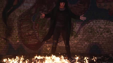 mysticism : Man in black clothes stands on a burning floor in an abandoned building with his arms open. Shooting a clip. Slow motion