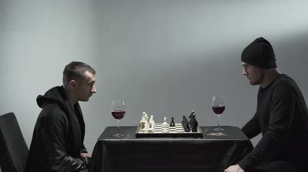 anlamı : Two male rockers in black clothes sitting in room with white walls with glasses of red wine and chessboard and withering each other. Stok Video