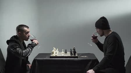 сценарий : Two man in black clothes sitting in room with glasses of red wine and chessboard and withering each other. Leisure to play chess.