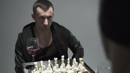 сценарий : Portrait of a man sitting in front of a chessboard and a wine glasses. A guy in black clothes thinks about his move in a chess game. Leisure to play chess.