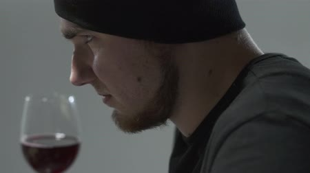 сценарий : Side portrait of a bearded guy sniffing wine in a wine glass. Leisure of young man.
