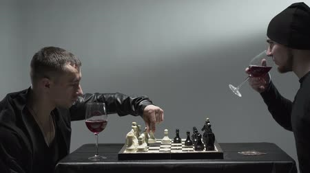 turbina eólica : Two male rockers in black clothes sitting in room drinking red wine and playing chess hated each other