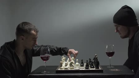 significado : Two man in black clothes sitting in room drinking red wine and playing chess hated each other