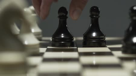 hatred : Close-up of chess board with white and black chess pieces. During a tense tournament, the opponent takes a pawn.