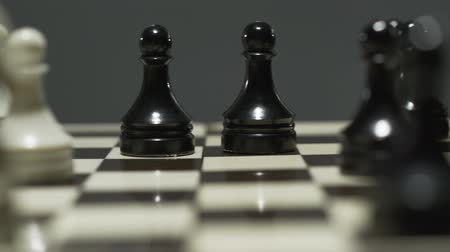 hatred : Chess board with white and black chess pieces. During a tense tournament, the opponent takes a pawn. Close-up
