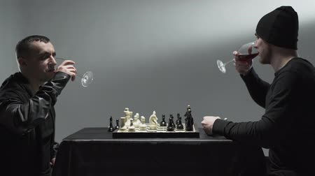 reunir : Two men in outerwear playing chess sitting at the table with the glasses of red wine. One guy throwing the card into an opponent, another guy gets up from the table and drops chess pieces on the floor