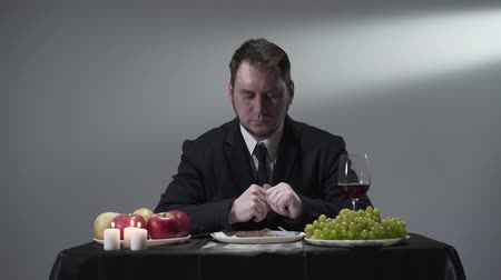 red tie : Rich businessman in a suit eatting or tasting a piece of meat next to apples, grapes and a glass of red wine.