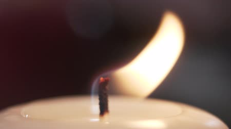 adwent : Close-up view of a burning candle. The flame waving on the wind, macro shooting. Romantic atmosphere