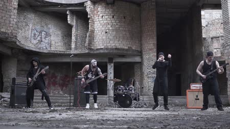 serseri : Rockers in gothic style and make-up playing metal rock with guitar and drum kit on the background of abandoned building
