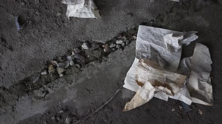 crumpled : Close-up crumpled book pages lie on the concrete floor of an abandoned building. The wine glass falls to the floor and breaks. Concept of destruction