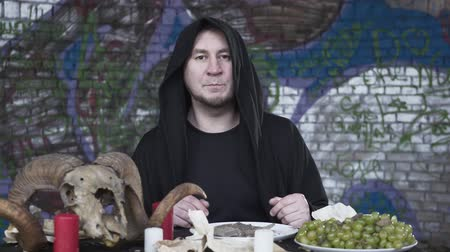 beran : Suspicious man in the black clothes with the hood on the head sitting at the small table in front of candles, grapes, and the ram skull, talking looking in camera. The dark witcher celebrating Dostupné videozáznamy