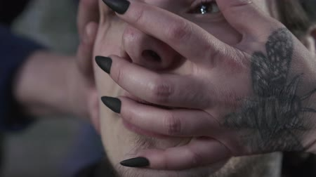 intrigue : Female and male hands with gothic tattoos and nail polish dramatically touching and stretching the male face