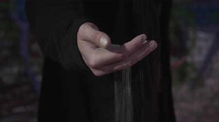 provést : Male hand with the sand close-up. The sand flows through the fingers of a man. Dark beauty concept Dostupné videozáznamy