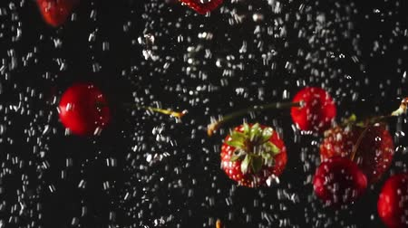 gracefully : Falling fresh strawberries and cherries splashing into sparkling water on black background. Close up Stock Footage
