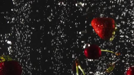 macro shooting : Falling fresh strawberries and cherries splashing into sparkling water on black background. Close up Stock Footage