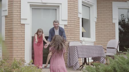 pozdravit : Happy family standing on the porch together. Mother and father greeted daughter who played with friends near the house, the child hugging parents. Summertime leisure Dostupné videozáznamy