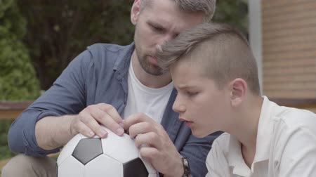 çözmek : Portrait of father and his son sitting on the porch holding a deflated soccer ball in hands close-up. The dad helping the boy to fix the ball. Family spending time together. Summertime leisure