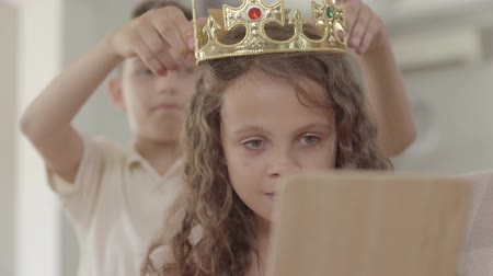 príncipe : The boy putting the crown on the head of curly girl looking in the mirror. The crown is too big for the child, kids laughing. Gallant boy caring for a beautiful girl Stock Footage