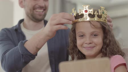 adore : Portrait father putting the crown on the head of curly girl looking in the mirror. Daddy adores his daughter. Father treats his daughter like a princess