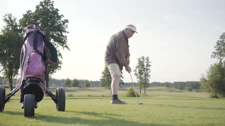 golfjátékos : Mature man playing golf on the golf field. Senior man hit the ball using golf club. Old gentleman playing game outdoors. Summer leisure