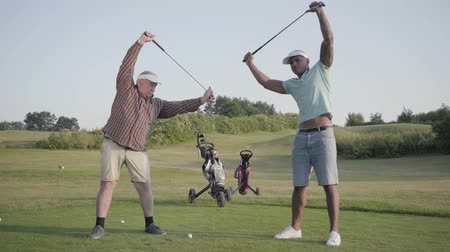 точность : Mature Caucasian man and young middle eastern man playing golf on the golf field. Players warming up before the game, holding golf clubs over their heads. Summer leisure
