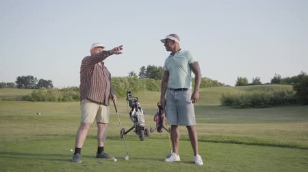 outdoor hobby : Mature Caucasian man and young middle eastern man playing golf on the golf course. Men gesture to the side, look and discuss. Summer leisure. Stock Footage
