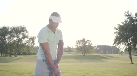 teljes hosszúságú : Portrait successful middle eastern golfer swinging and hitting golf ball on beautiful course. Confident man golfing in beautiful sunny summer weather standing in the sunshine.