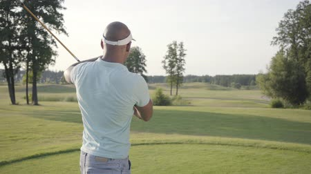 golfe : Portrait handsome successful middle eastern golfer swinging and hitting golf ball on beautiful course. Confident man golfing in beautiful sunny summer weather standing in the sunshine. Vídeos