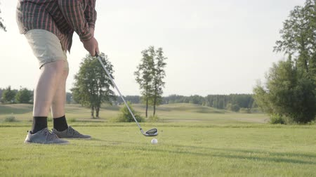 klub : Unrecognized man playing golf hitting golf ball on the golf course. The concept of recreation and sports outdoors.