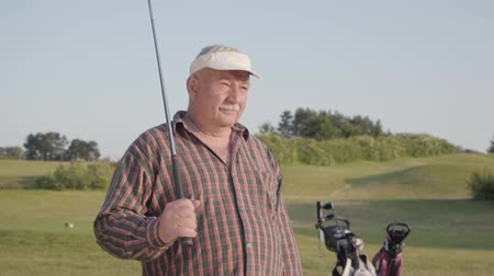 ゴルファー : Mature man playing golf on the golf field. Senior man looking away putting the club on his shoulder. Old gentleman playing game outdoors. The concept of recreation and sports outdoors. Slow motion 動画素材