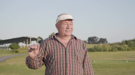 концентрированный : Successful mature man with a golf club standing on a golf course in good sunny weather. Portrait senior golfer. Sport and leisure outdoors. Slow motion