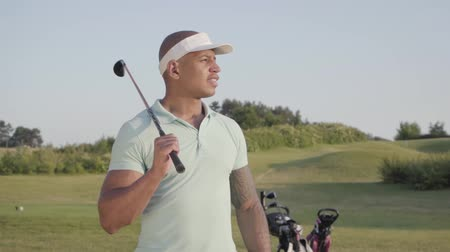 ゴルファー : Portrait cute smiling confident successful middle eastern man with a golf club standing on a golf course in good sunny weather. Sport and leisure outdoors. Slow motion