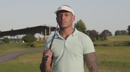 поле для гольфа : Young concentrated middle eastern man looking away with the golf club on his shoulder. Handsome man playing golf on the golf field. Summer leisure. Slow motion