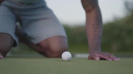 ゴルフ : Young middle eastern man playing golf on the golf field. Handsome man blowing on the golf ball which lies in the edge of the hole and making it fall. Summer leisure