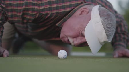 ゴルファー : Mature man is trying to blow a golf ball in the hole. The concept of recreation and sports outdoors.