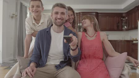 family watching tv : Portrait happy adorable family watching TV at home together. The father holds the remote and switches the channels, the wife sits next to her husband and two children are with their parents. Family leisure. Stock Footage