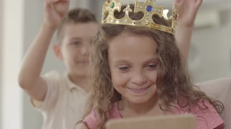 príncipe : Cute boy putting the crown on the head of adorable curly girl looking in the mirror. Gallant boy caring for a beautiful girl. Relationship brother and sister.