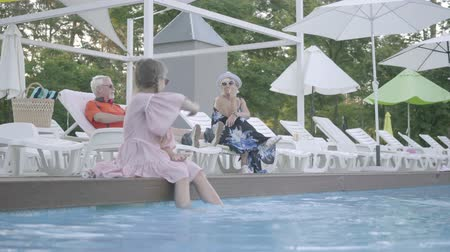 サンベッド : Old couple lying on sunbeds near the pool on the background. Little funny girl with pigtails sitting on the edge of the pool with her feet in the water. Happy friendly family. Rest in hotel