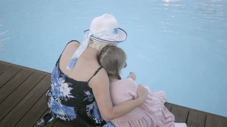косички : Back view of little funny girl with pigtails and mature woman sitting on the edge of the pool. Rest and leisure of grandmother and granddaughter. Happy friendly family.