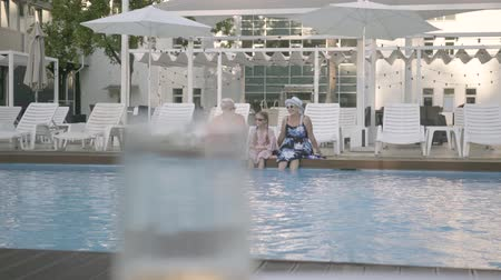 starszy pan : Fun happy mature couple with little granddaughter sitting on the edge of the luxury pool. Grandmother, grandfather and grandchild converse. Happy friendly family. Rest in hotel. Recreation and leisure outdoors
