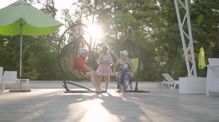 бабушка или дедушка : Little cute girl with pigtails wearing a summer dress and sunglasses standing with a tablet next to her grandparents sitting in hanging chairs.