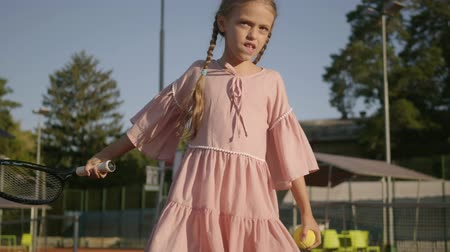 tennis rackets : Adorable funny girl with two pigtails playing tennis outdoors. Concentrated child holding a racket and ball about to pass. Summertime leisure Stock Footage