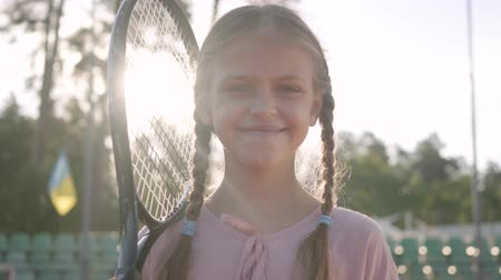 teniszütő : Portrait cute little smiling girl with pigtails and a tennis racket on her shoulder looking into the camera standing in the rays of the summer sun. Recreation and leisure outdoors. Stock mozgókép
