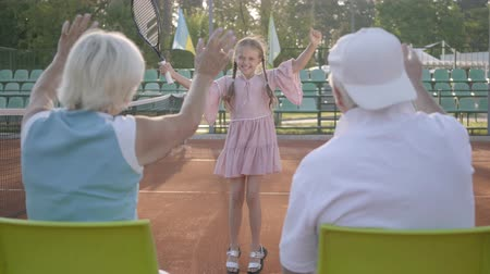 won : Cute funny girl with two pigtails won the tennis tournament. Her grandparents sitting near with their backs to camera supporting granddaughter. Lovely child raising racket up in a winning gesture