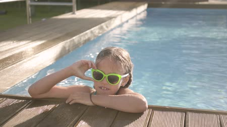 inclusive : Portrait pretty funny girl in yellow sunglasses looking in the camera smiling, looking out of the pool, holding on to the edge. Child having fun in the hotel complex. Recreation and leisure outdoors. Stock Footage