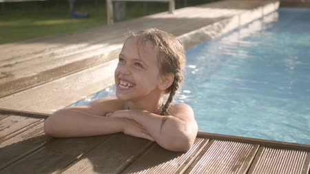 blue braid : Cute funny girl with pigtails laughing, showing thumb up looking out of the pool, holding on to the edge. Preteen child having fun in the hotel complex