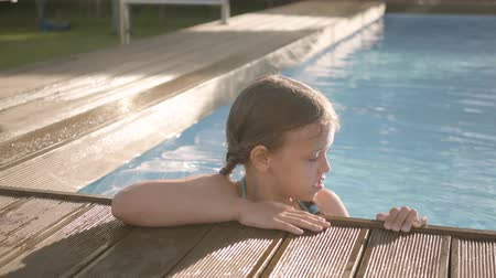 blue braid : Adorable funny girl with pigtails laughing, showing thumb up looking out of the pool, holding on to the edge. Preteen child having fun in the hotel complex