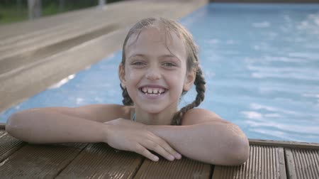 blue braid : Portrait cute funny girl with pigtails laughing looking in the camera. The child showing thumb up looking out of the pool, holding on to the edge. Preteen kid having fun in the hotel complex Stock Footage