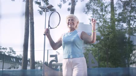 won : Joyful mature woman won the tennis tournament. The old lady jumping raising hands up with the racket in a winning gesture. Active leisure outdoors